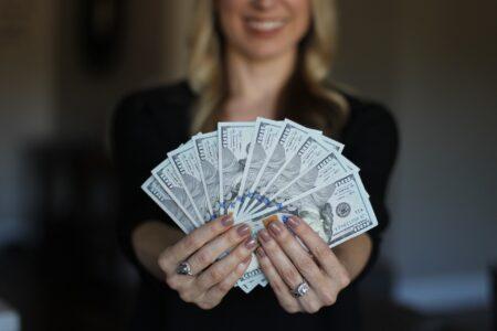 private money lender in Houston woman holding $100 bills